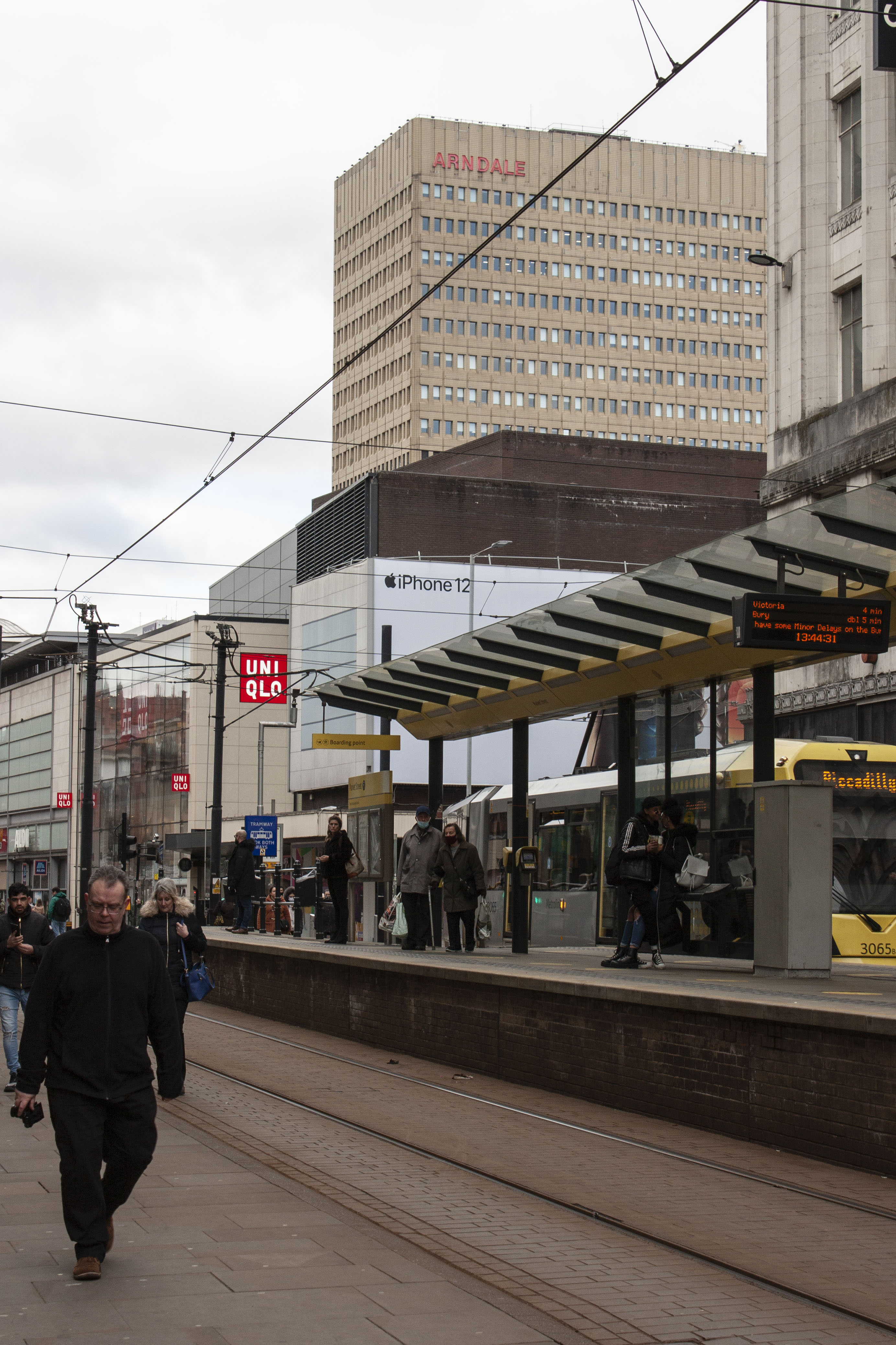 Busy tram stop in city centre with skyline visible