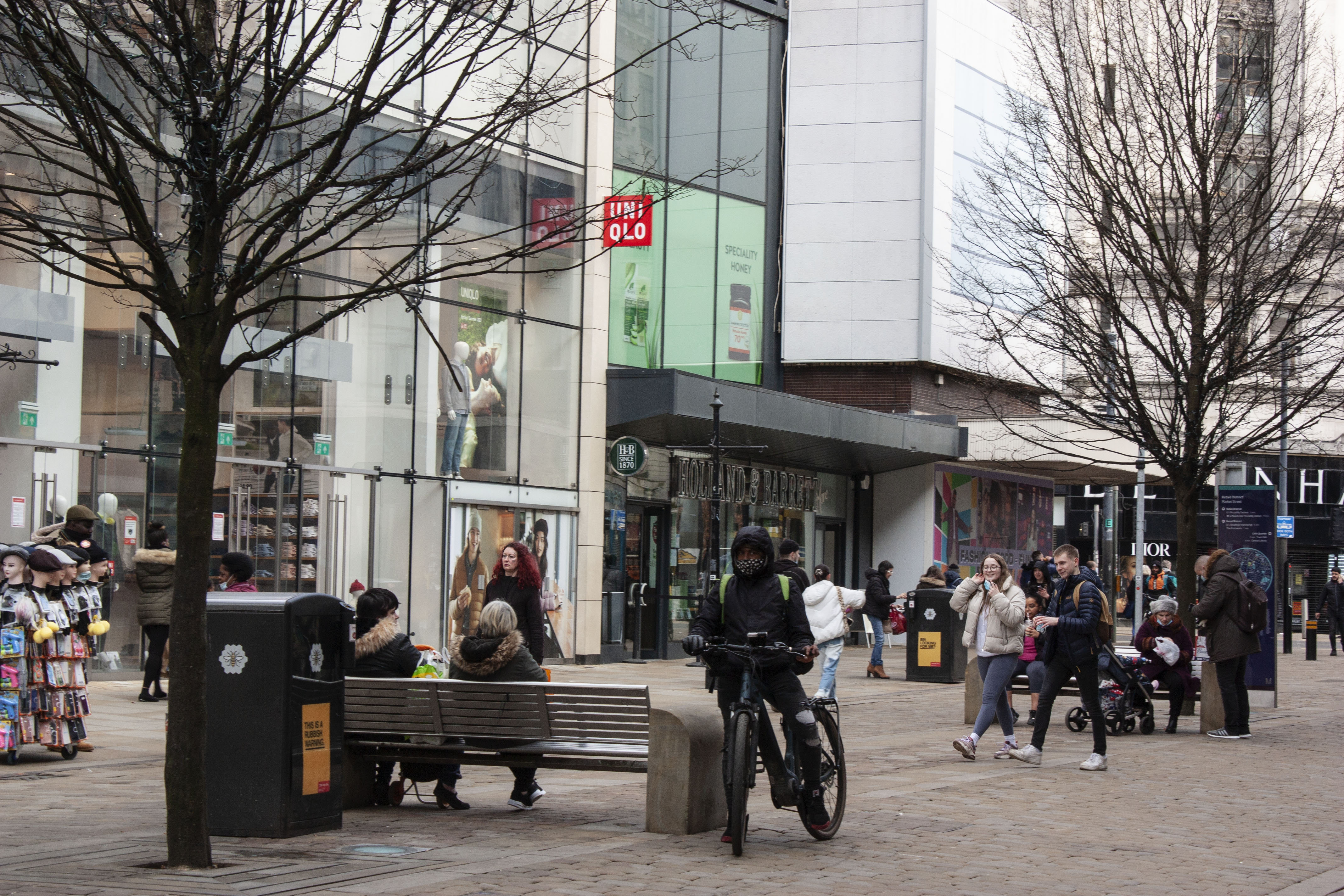 Public walking through busy city centre, man on bicycle as main subject
