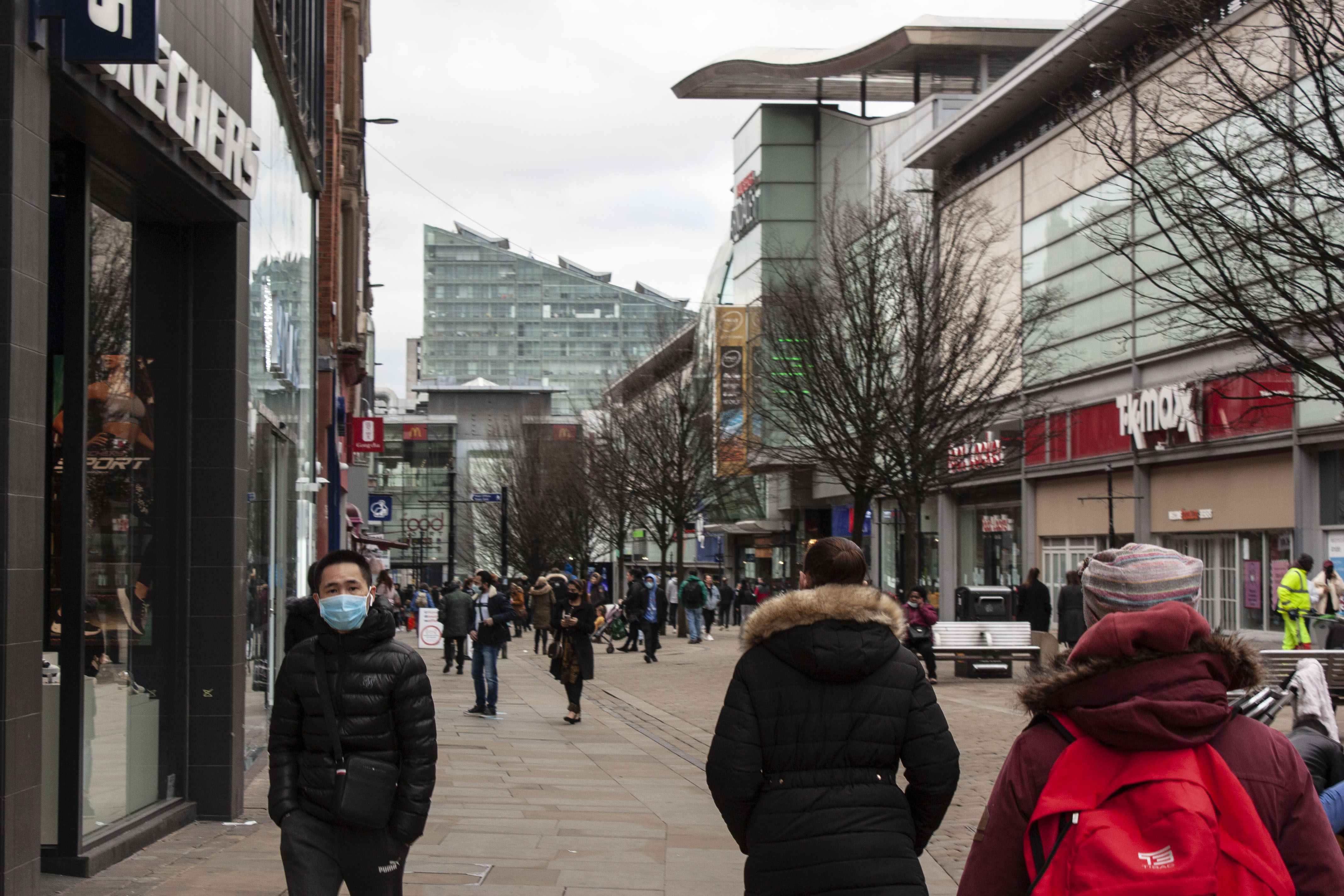 Busy city centre with a masked pedestrian as main subject