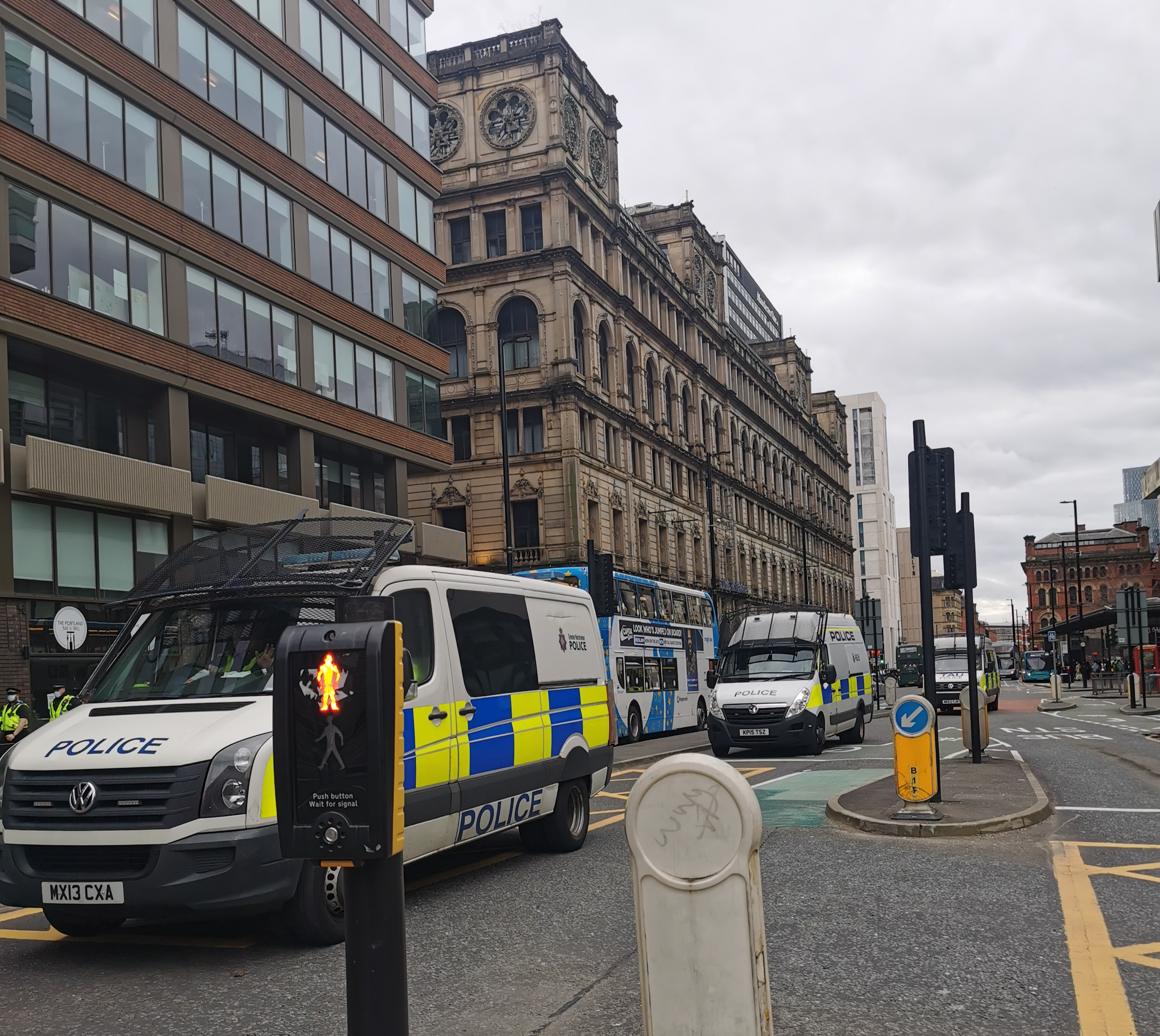 A convoy of three police vans drive to the Piccadilly Gardens sit in