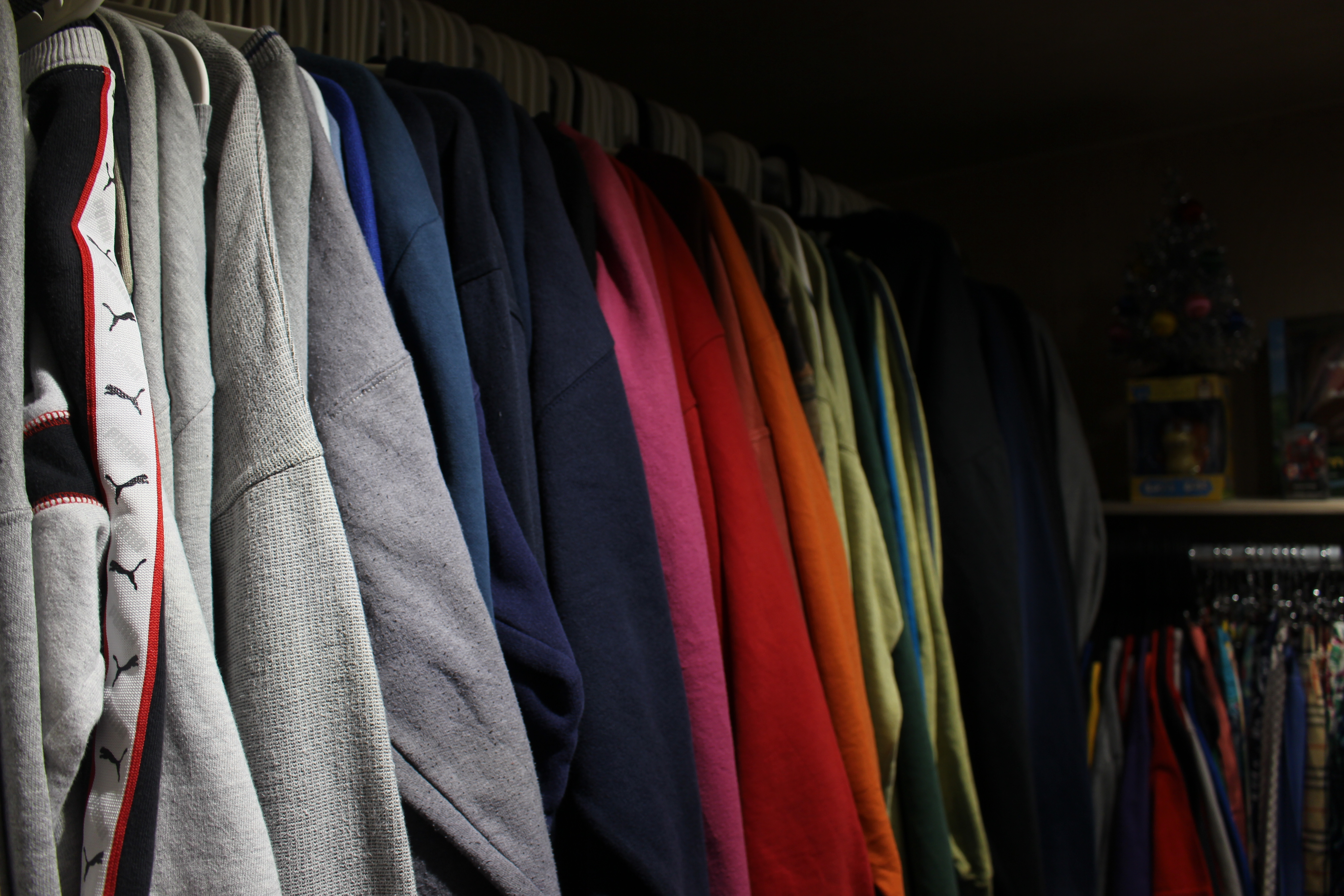 A clothing rail full of multi-coloured sweaters